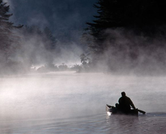 Photograph of a man rowing a boat down a river
